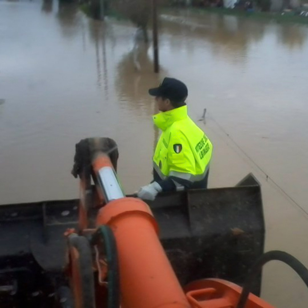 Italian National Civil Protection rescuer on a digger during a flooding