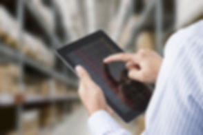 Businessman checking inventory in stock room of a manufacturing company on touchscreen tablet