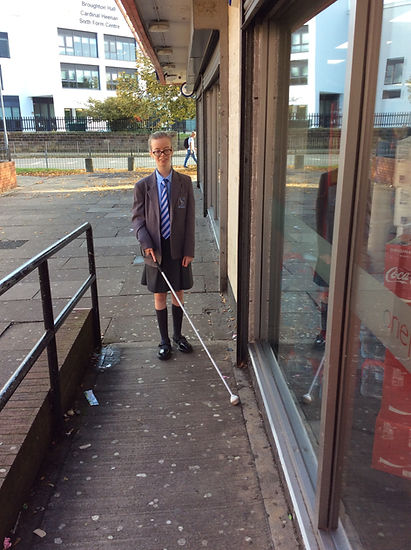 pupil using long cane on a ramp to the supermarket