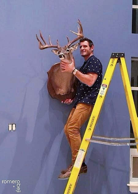 Chris hanging clients repurposed deer head in his new man cave.