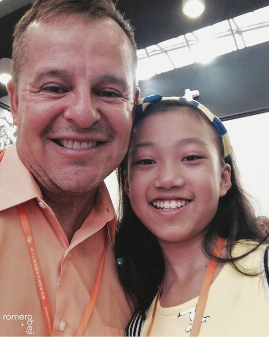 At trade show as guest American Designer in China with sweet girl who really wanted a pic with us.