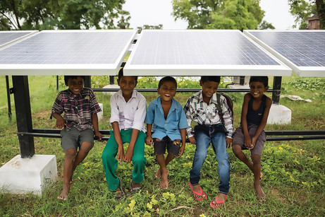 Children sit under solar panels at Bishu
