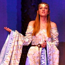 "This image is from CastleCo Theatre's production of ""King Arthur and Princess Arthena"". This image shows a woman in a blue dress from the middle ages. The dress has long sleeves and the woman is wearing a gold crown."