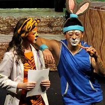 "The image is from CastleCo Theatre's production of ""The Jungle Book."" The image shows an actor dressed as a tiger talks to an actor who is dressed as a rabbit."
