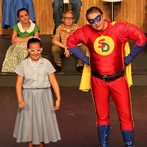 "This image is from CastleCo Theatre's production of ""Homer Price"". The image shows an actors dresses as a super hero talking to a girl dressed in clothing from the 1950s."