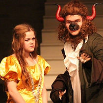 "This image is from CastleCo Theatre's production of ""Beauty and the Beast"". This image shows an actor dressed up in a beast costume (with horns and brown fur), talking to a girl dressed up in a fancy gold dress."