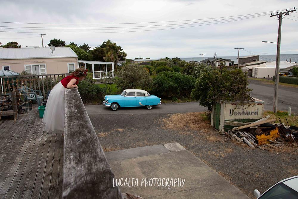 junior bridesmade leaning over railing watching wedding car arrive, Ngawi Wairarapa wedding photographer