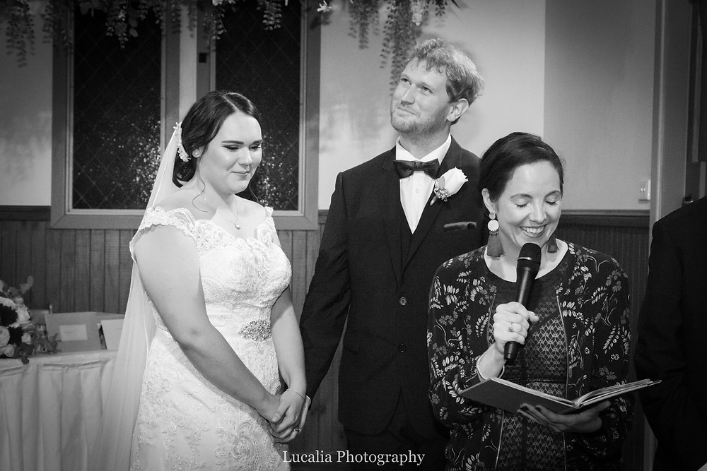 black and white photo of a bride and groom with wedding celebrant all smiling, Lucalia Photography
