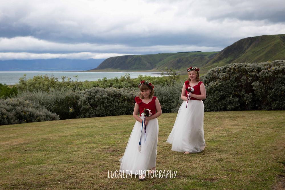 Junior bridesmaids walking across lawn with ocean view, Waimeha Camping Village, Ngawi, Wairarapa wedding photographer