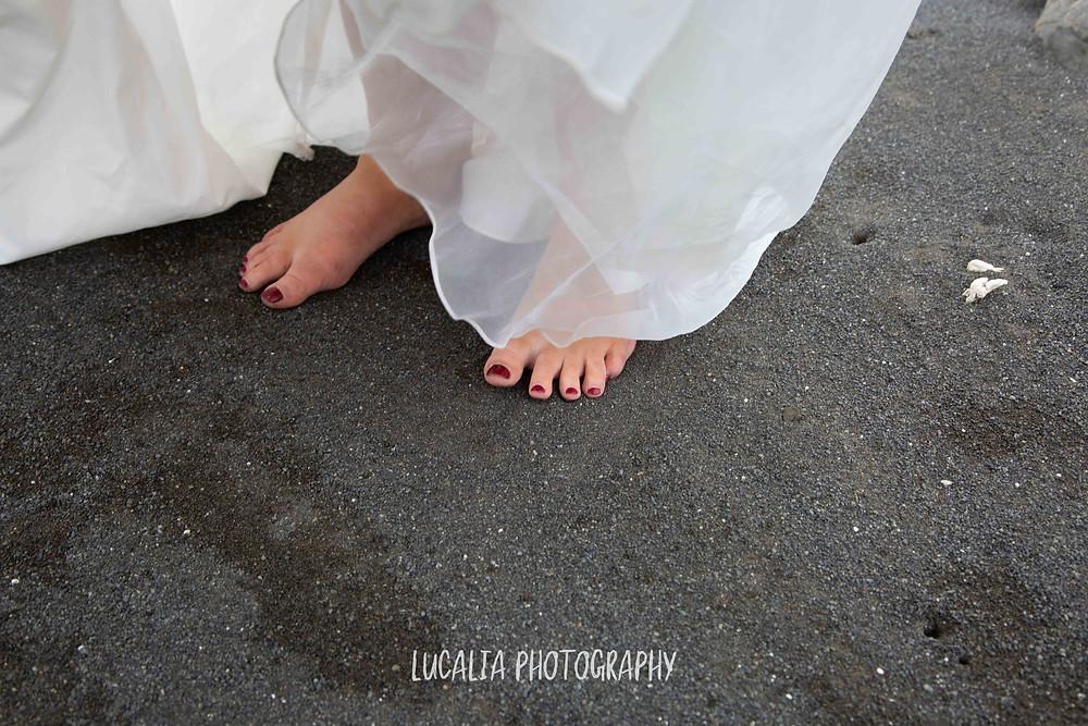 barefoot bride walking on black sand beach Ngawi, Wairarapa wedding photographer