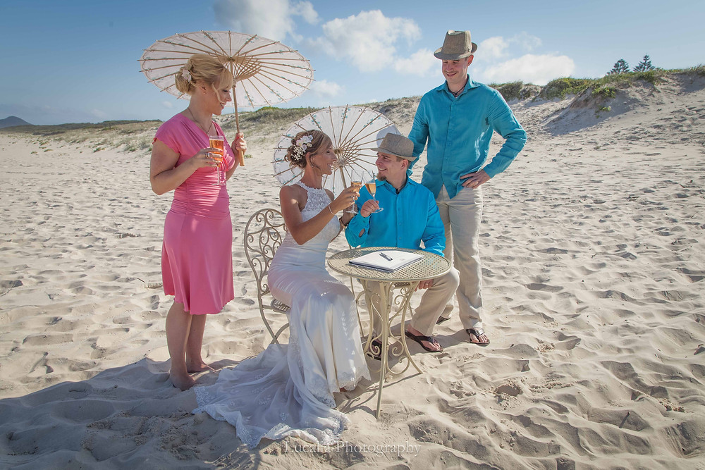 married couple after signing the marriage certificate on a beach with champagne