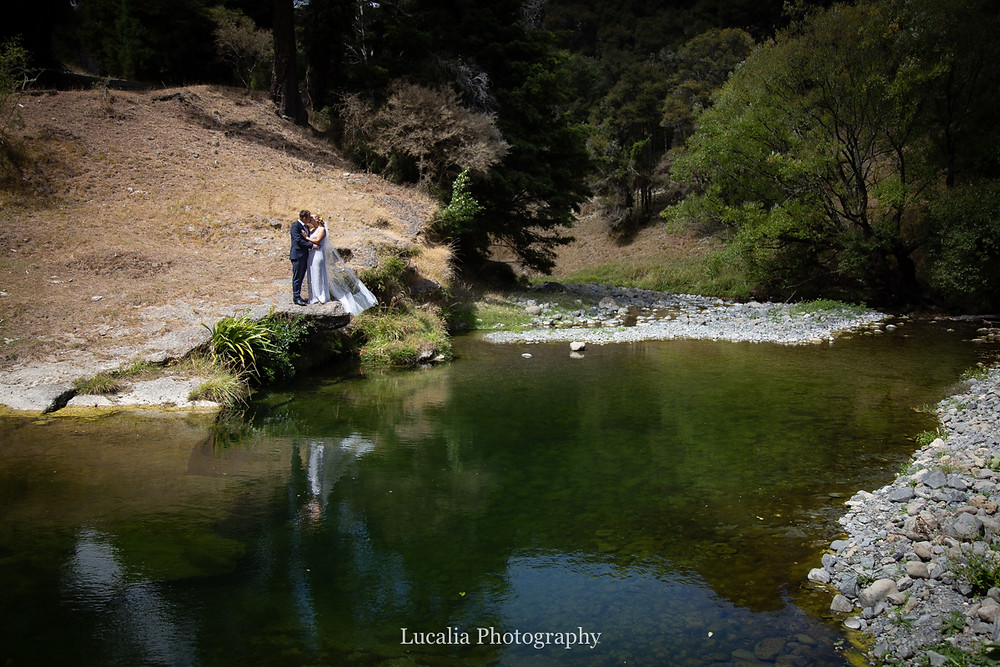 bride and groom adventure portrait on river bank, Wairarapa wedding photographers