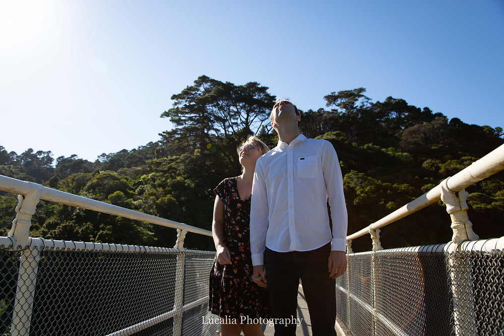 engaged couple looking up at the birds, on the dam wall, Zealandia, Wellington