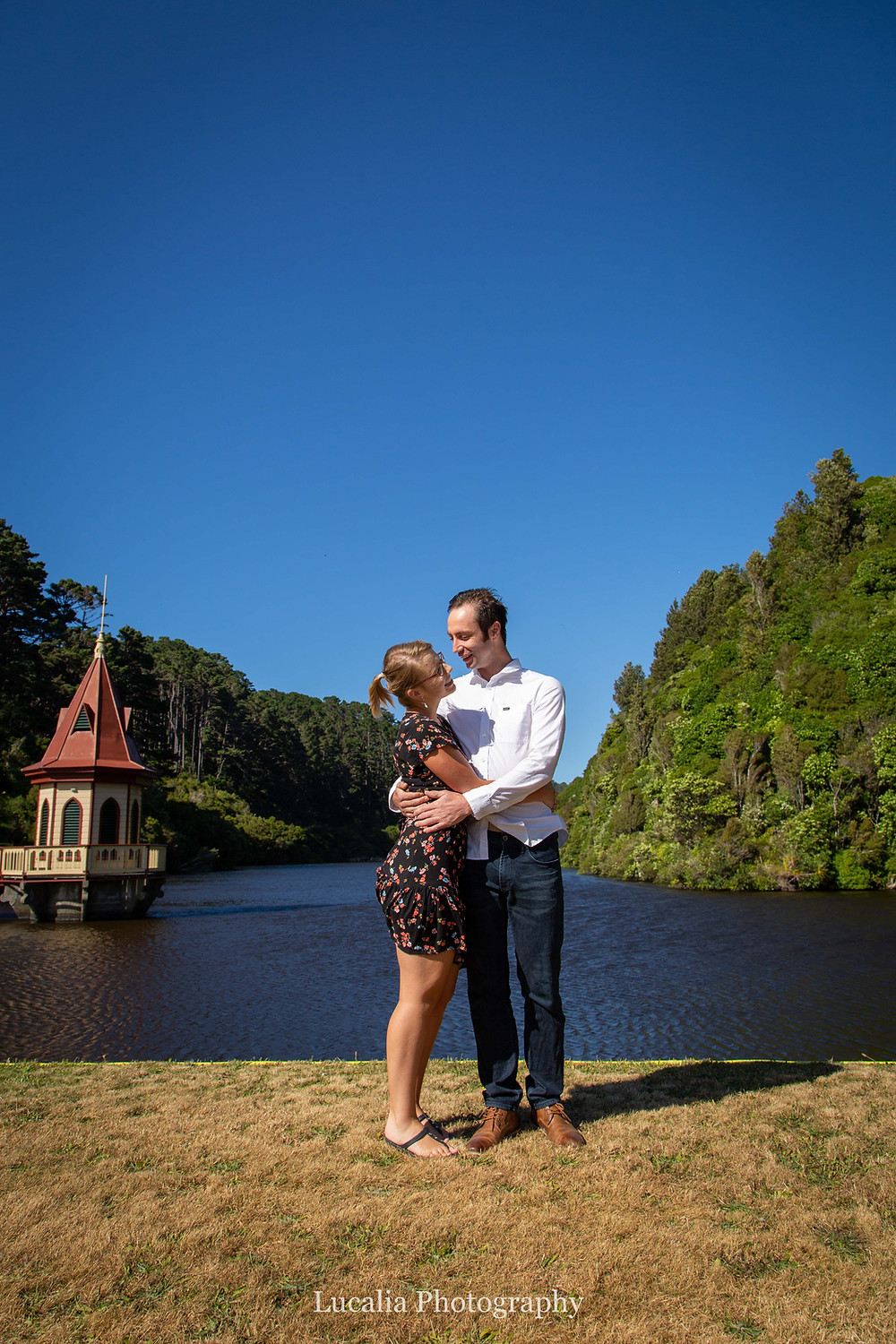 engaged couple hugging in front of reservoir and tower, Zealandia, Wellington