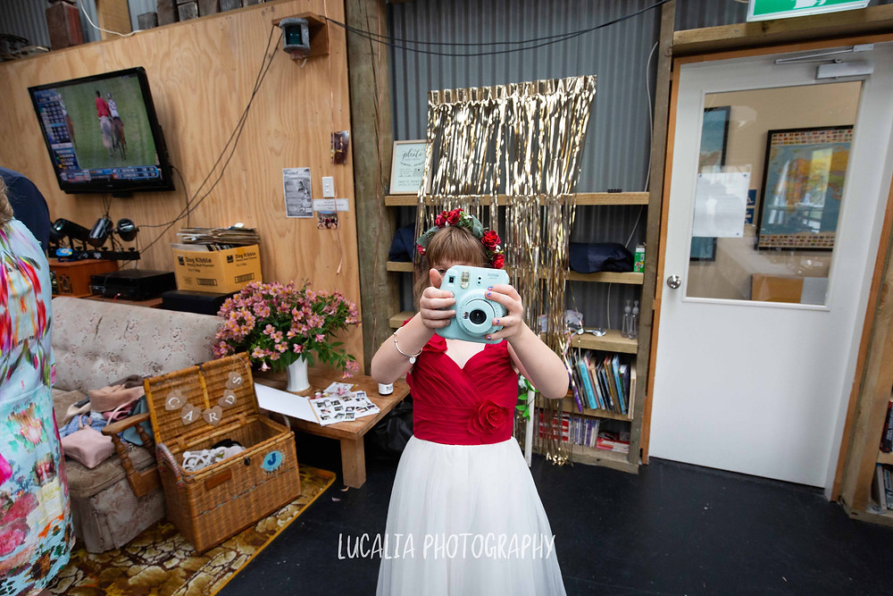 junior bridesmaid taking a photo with polaroid camera, Waimeha Bar and Grill, Ngawi Wairarapa wedding photographer