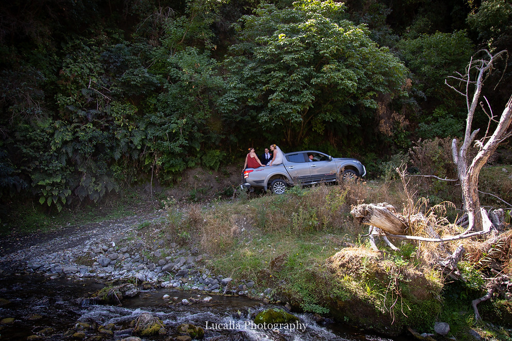 wedding party in tray of ute driving up steep road from river, Wairarapa wedding photographers