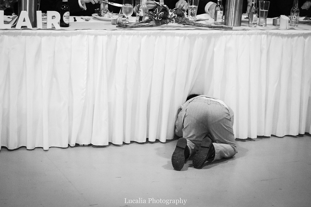 a child guest at a wedding crawls underneath the wedding party table, Lucalia Photography