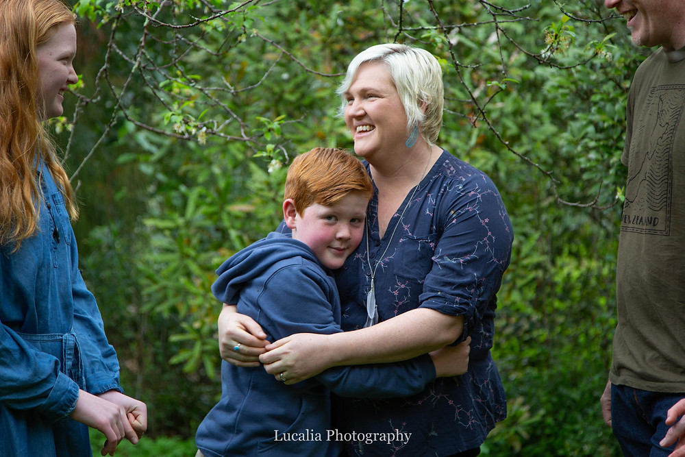 son hugging mum framed by sister and dad smiling, Wairarapa family photographer