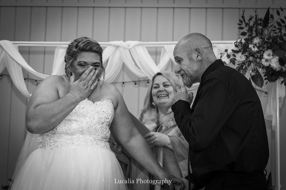 bride laughing with celebrant and groom saying shh during wedding ceremony, Wairarapa wedding photographer
