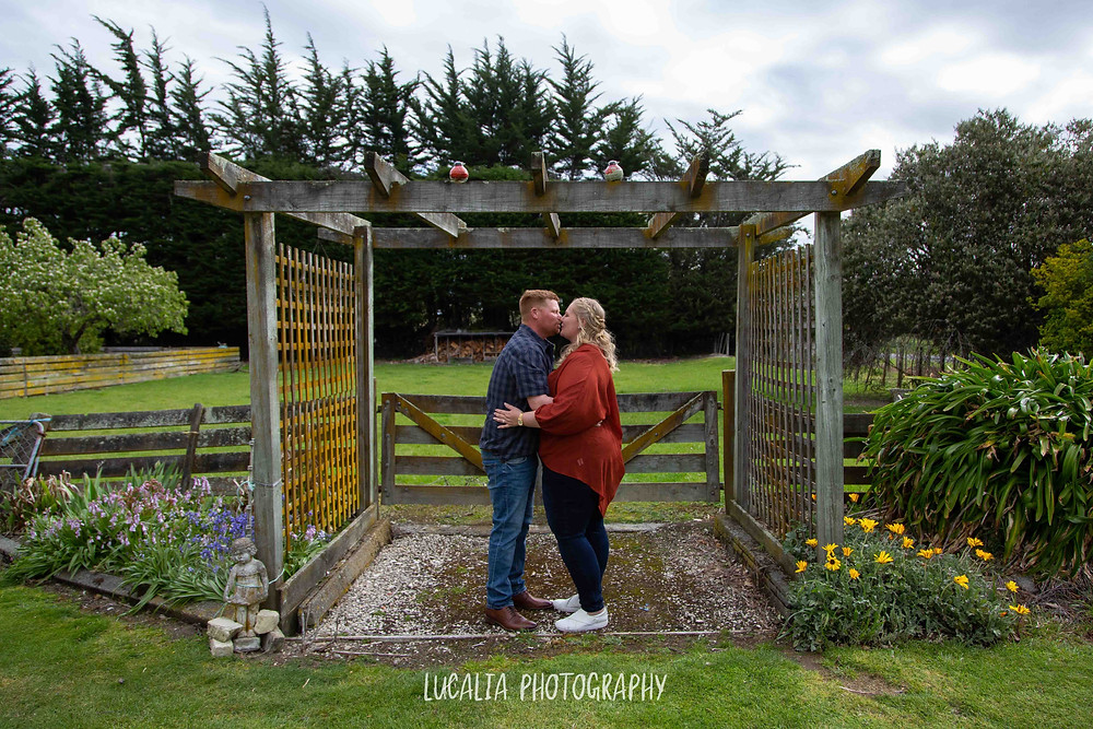 engaged couple kissing under a pergola, Wairarapa wedding photographer