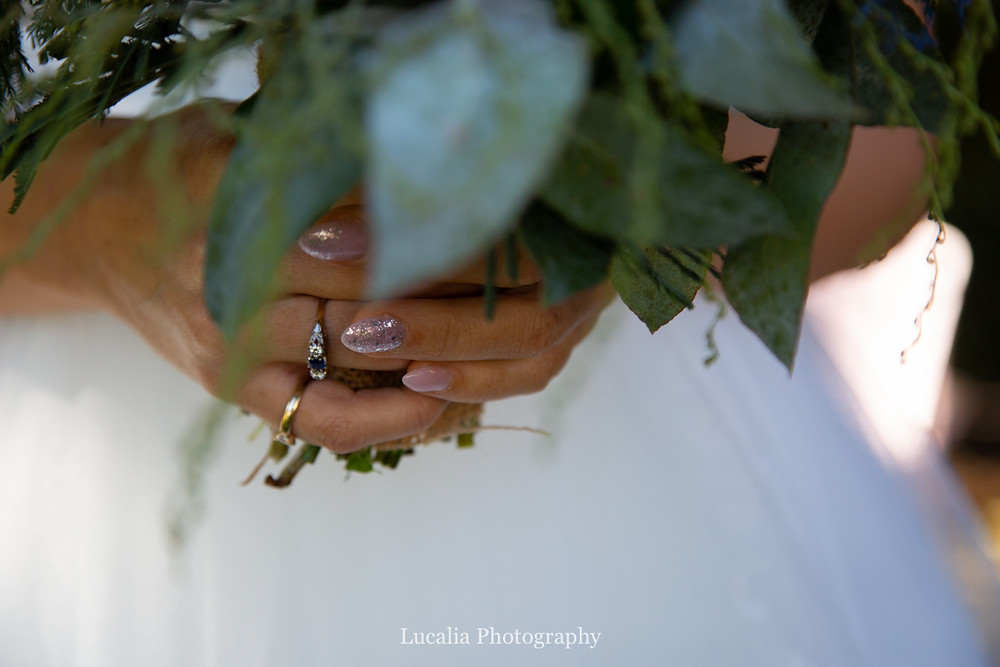 detail of brides hands holding leafy bouquet, Wairarapa