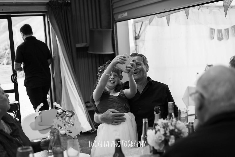 junior bridesmaid with wedding guest and polaroid camera, Waimeha Bar and Grill, Ngawi Wairarapa wedding photographer