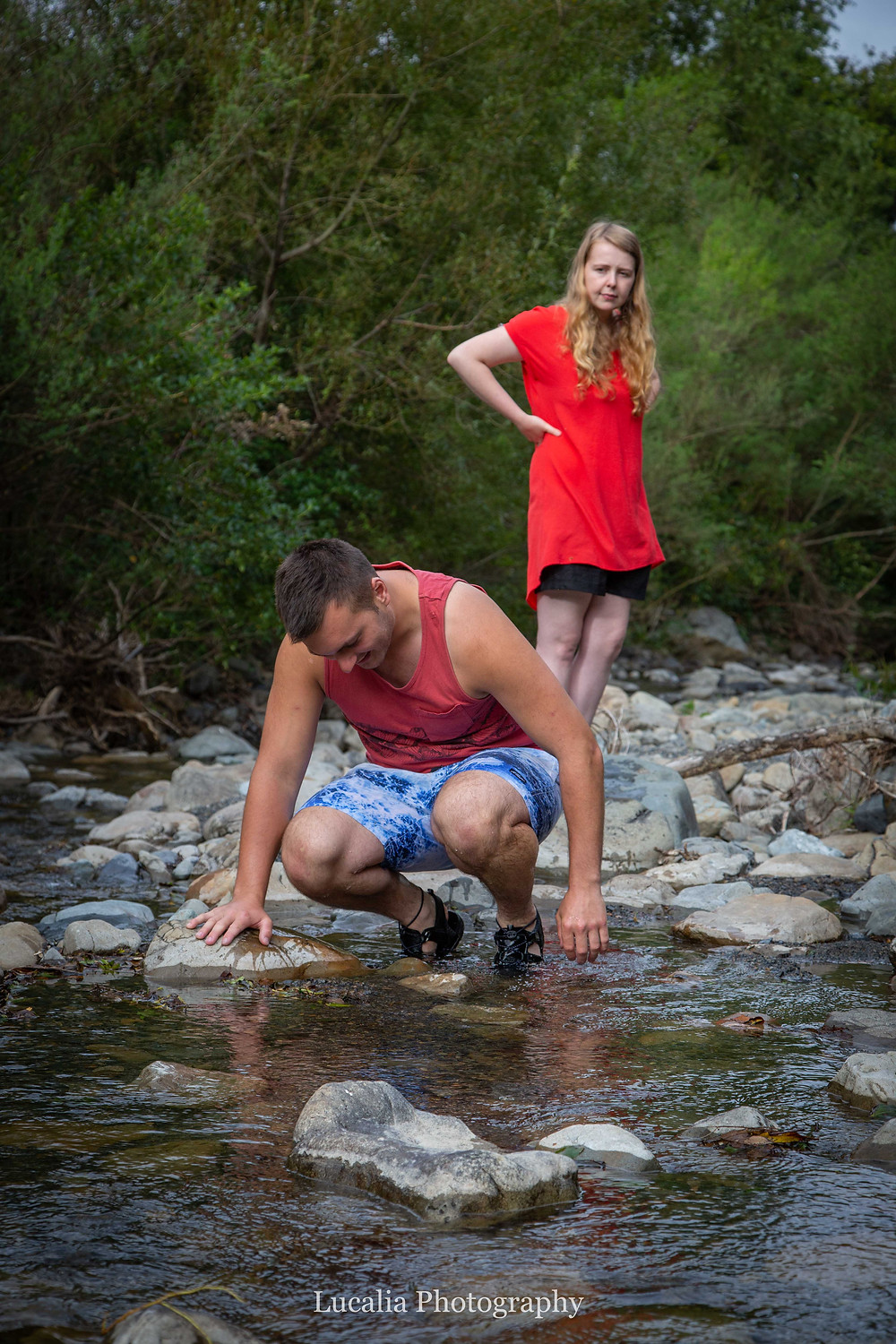 fiancee standing watching her husband to be crouching down to the water, Featherston Wairarapa