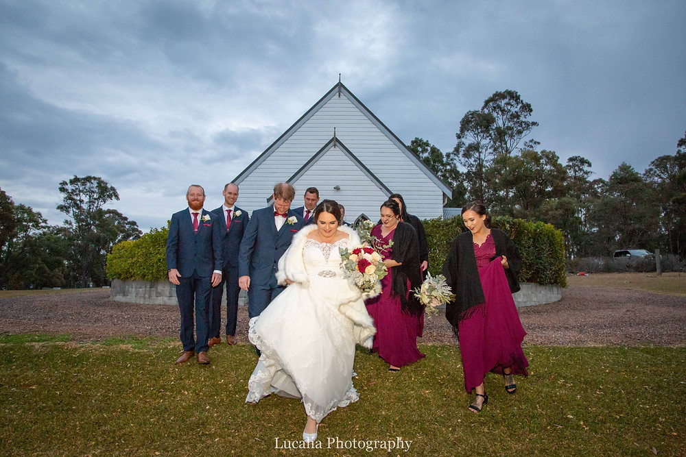 bride wearing white fluffy cape with wedding party at winter wedding, Wairarapa wedding photographer