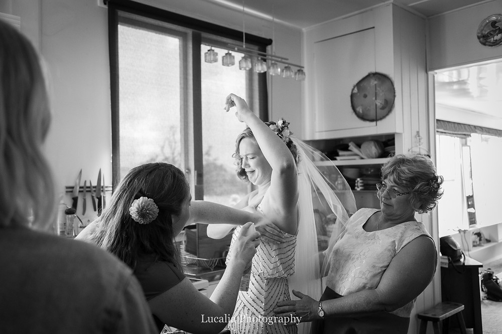 friends assist bride apply deodorant pulling face, Wairarapa wedding photographers