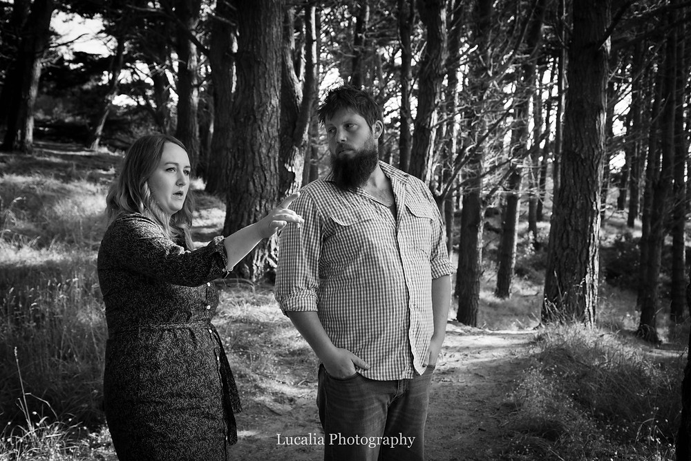 fiancee pointing with her husband to be looking on, in a pine forest, Castlepoint Wairarapa
