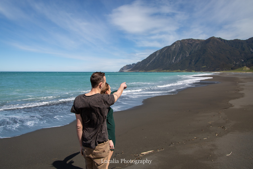 partner pointing along the beach to where he proposed, Wairarapa wedding photographer