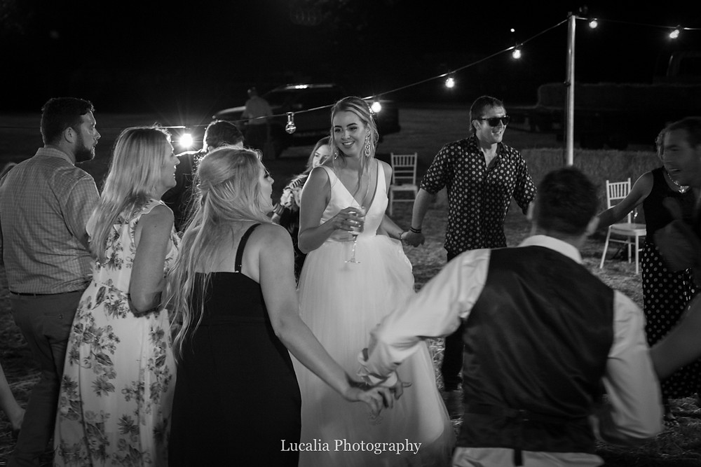 bride dancing in a circle of friends at night with festoon lights, Wairarapa