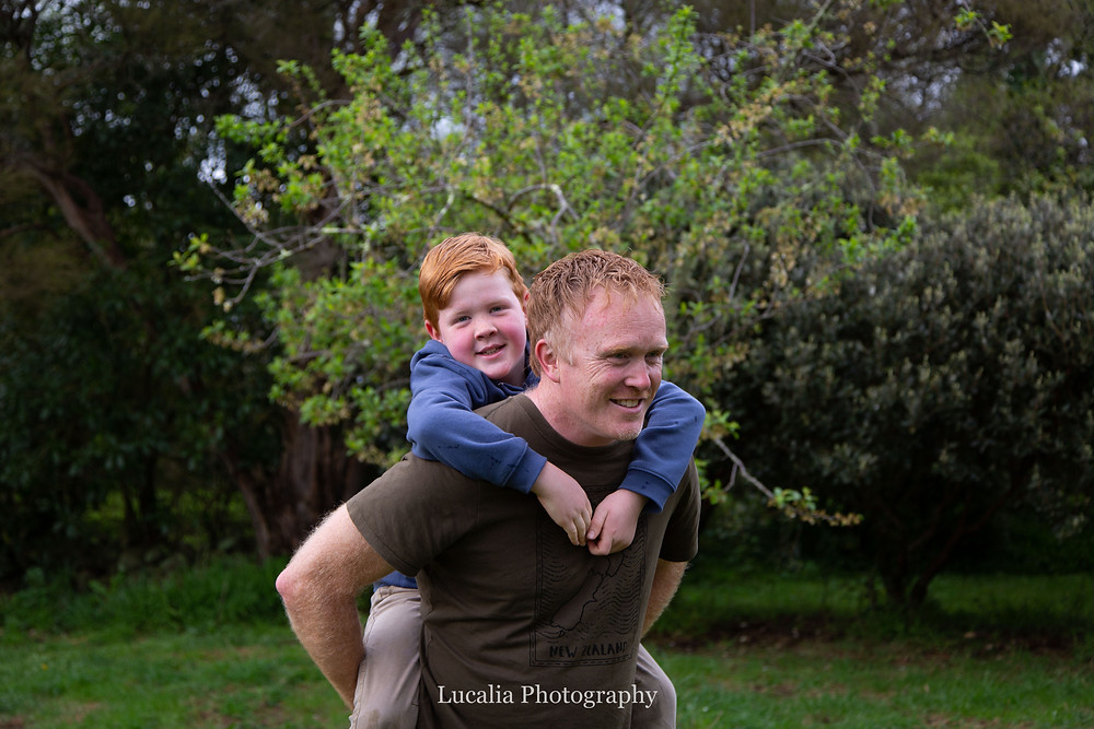 son having a pigging back with dad in orchid, Wairarapa family photographer