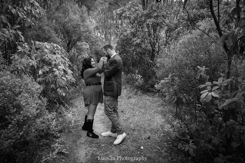 guy kissing fiancee's hands in a forest clearing, Wairarapa
