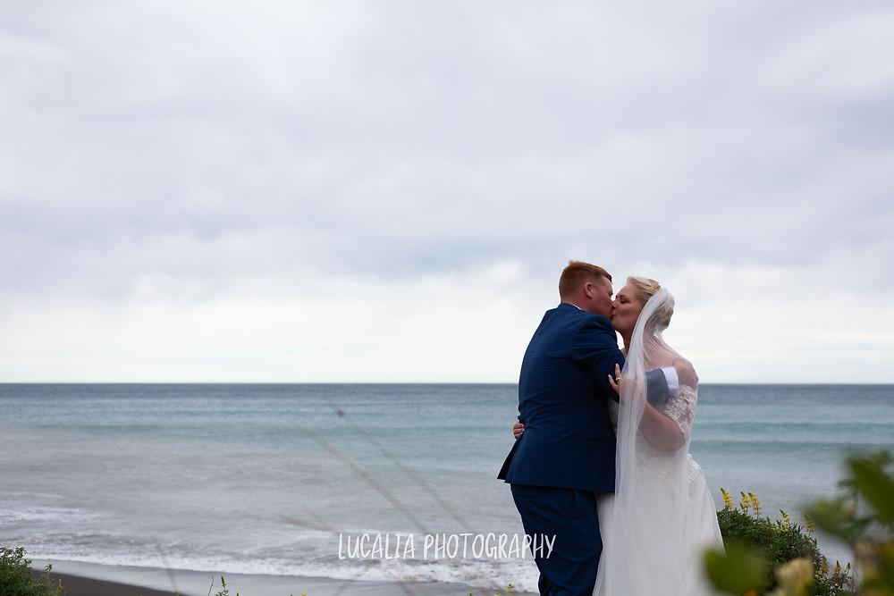 bride and groom kissing by beach Ngawi, Wairarapa wedding photographer