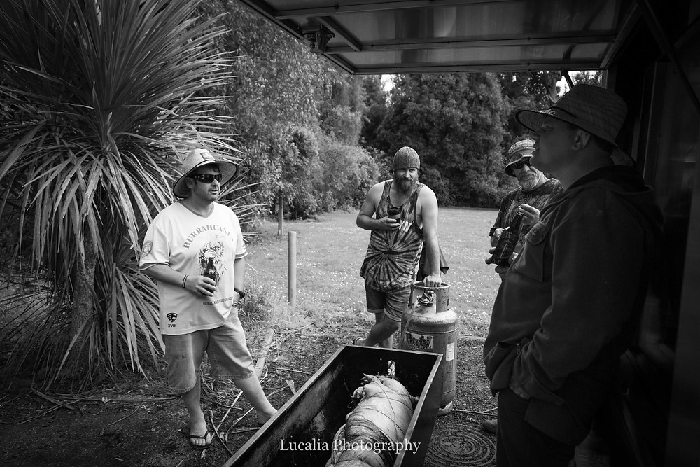 groom and groomsmen talking in the forest whilst food cooks, Wairarapa wedding photographer