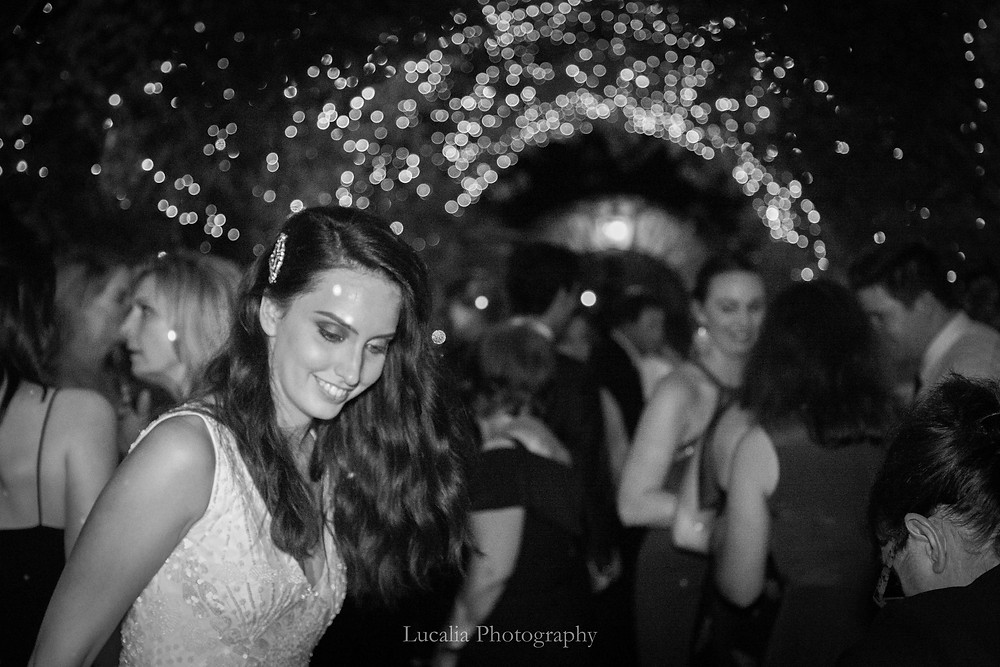 bride on dancefloor with guests and fairy lights