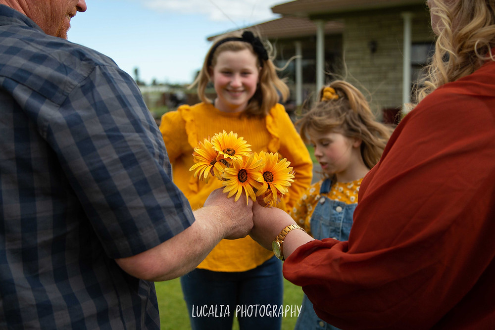 daughters giving dad and fiance yellow flowers, Wairarapa wedding photographer