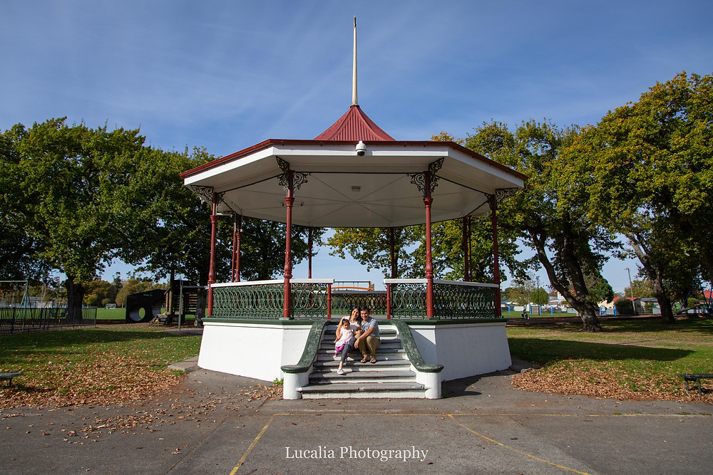 family sitting on the steps of the rotunda at Carrington Park, Carterton, Wairarapa