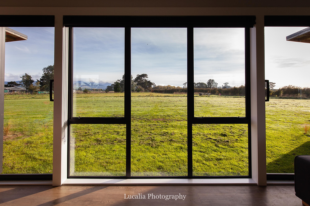 view through windows across grass to trees and Tararua mountains, Wairarapa