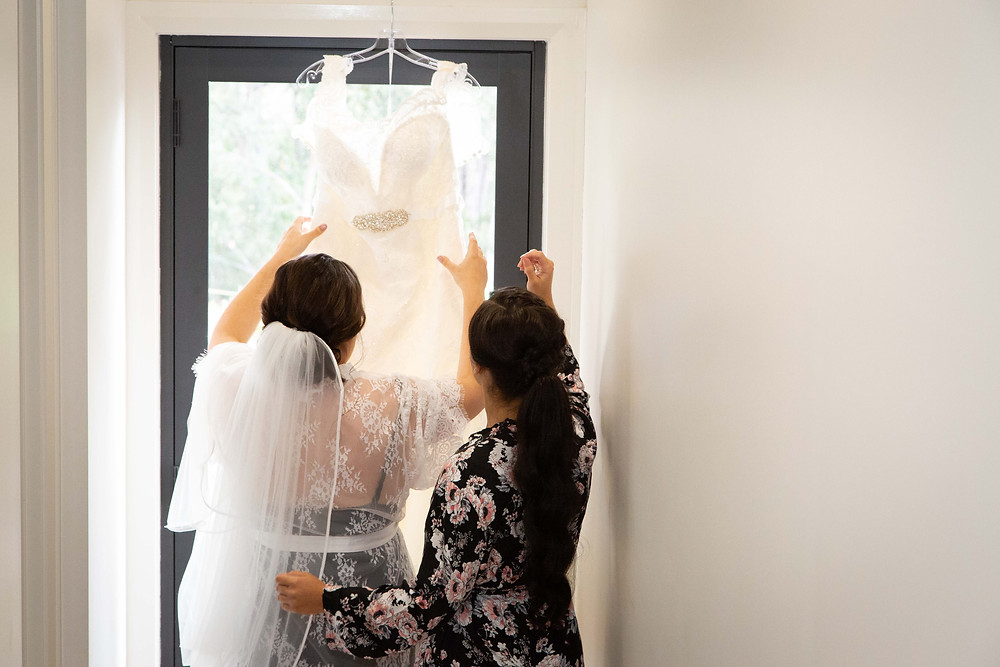 Bride and bridesmaid hanging a wedding dress in a hallway, Wairarapa