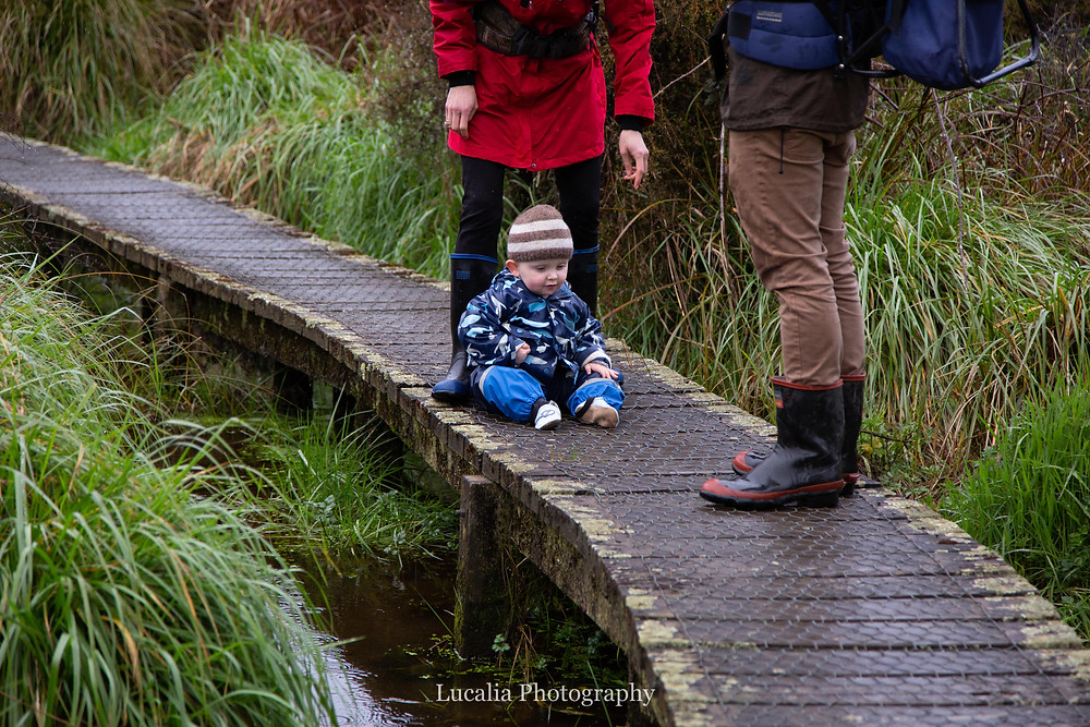 boy sits on boardwalk with legs of parents, Wairarapa family photographer