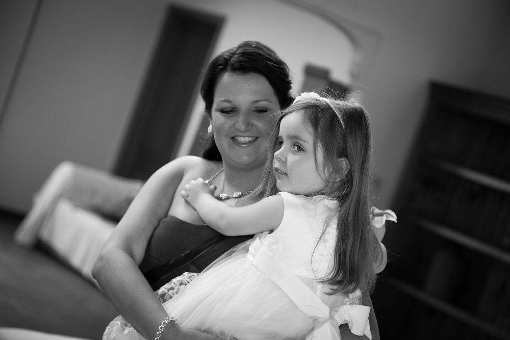 bridesmaid holding a flower girl in her arms smiling