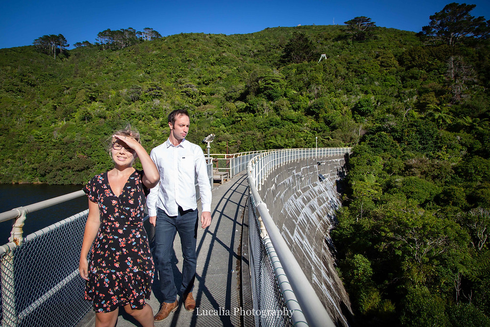 engaged couple walking along the dam wall in sunshine, Zealandia, Wellington