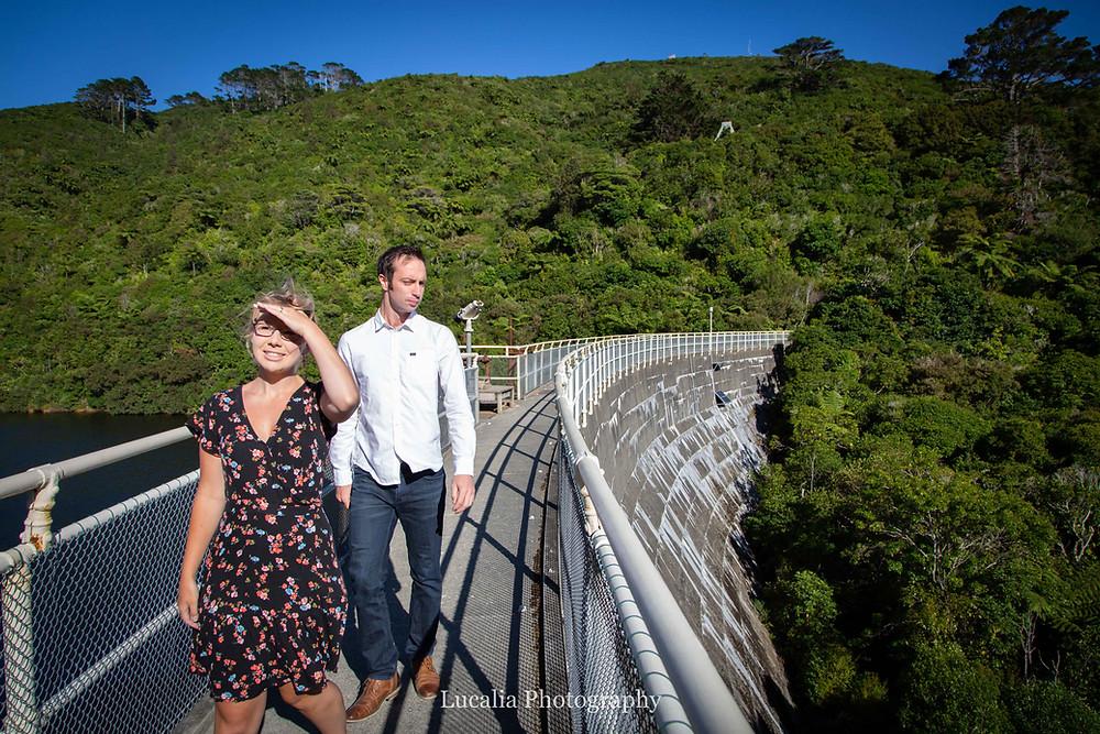 engaged couple walking along the dam wall in sunshine, Zealandia, Wellington