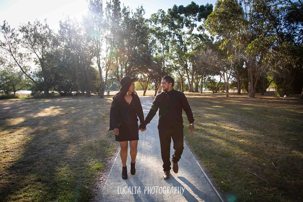 engaged couple walking along a path at Henley Lake holding hands, Wairarapa wedding photographer