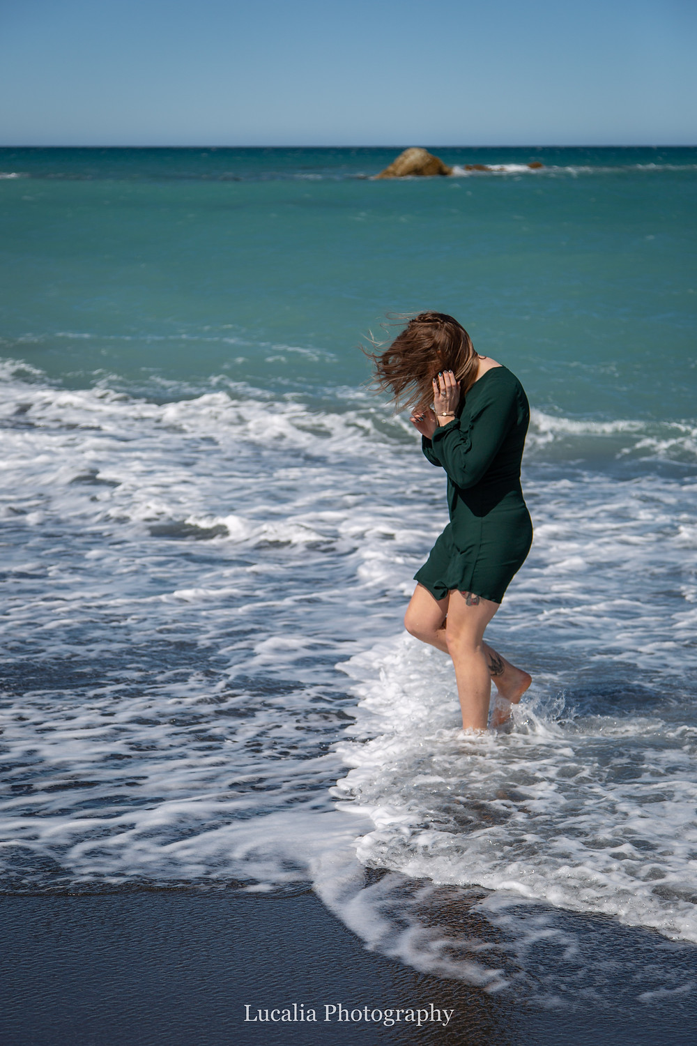 bride-to-be washing her legs in the ocean at White Rock beach, Wairarapa wedding photographer