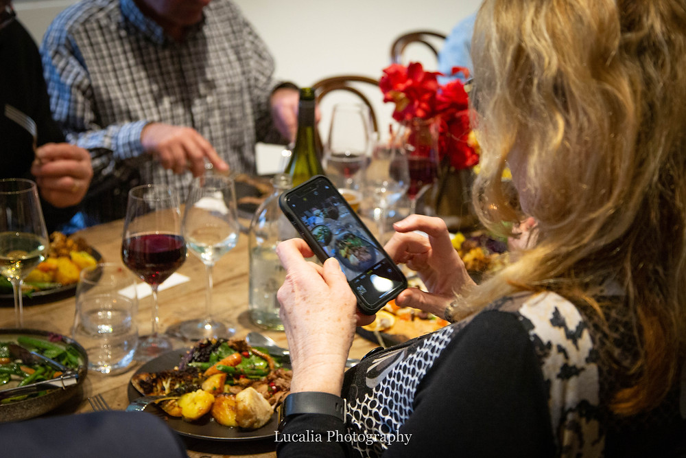 guest taking a photo of her food on her phone at Rose & Smith at Tauherenikau Wairarapa wedding venue