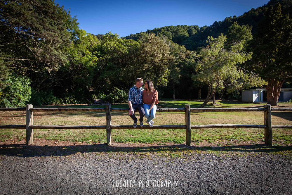 couple sitting on a fence looking at each other, Mt Holdsworth, Wairarapa wedding photographer