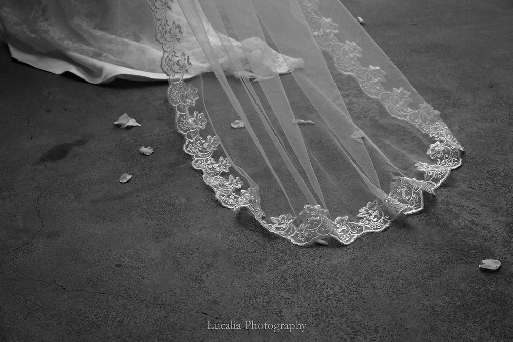 black and white wedding veil on concrete floor outside with rose petals